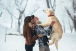 young-couple-holding-dog-outside