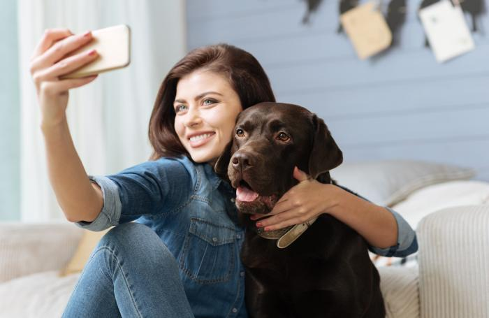 Girl taking selfie with dog