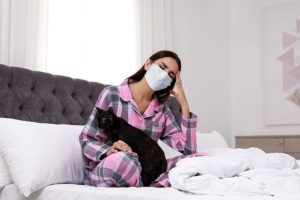 face-mask-woman-black-cat-bed-sick-COVID-pandemic.jpg