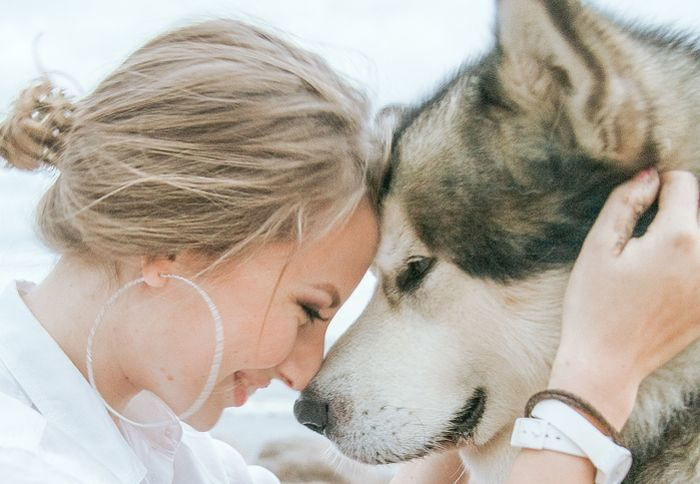 woman with dog touching foreheads