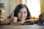 Thumbs up student on books
