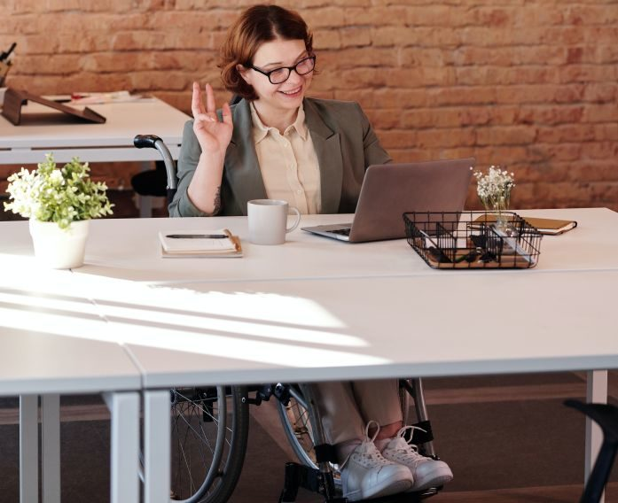 woman in wheelchair sitting at a table looking at her computer
