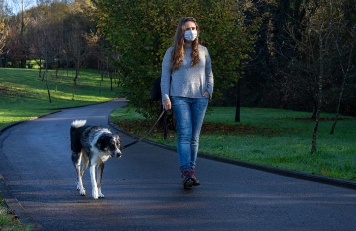 Woman-with-mask-on-walking-dog