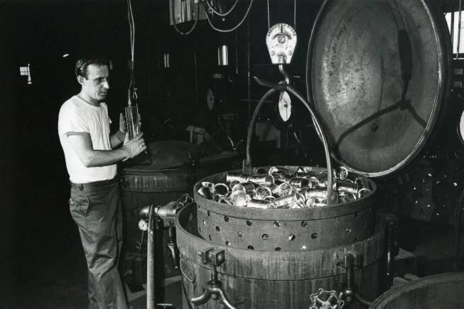 Factory worker standing next to barrel of cat food cans