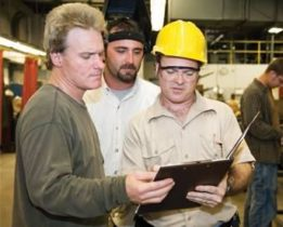 Three pet food safety workers looking at a clipboard